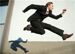 man sprinting ahead of his shadow